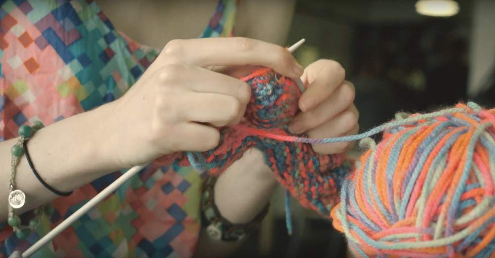 Close up of hands knitting a colourful yarn